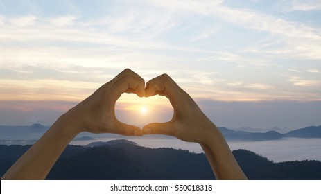 Heart shape. Mountain tourism. Symbol of love. Girl on a background of mountains. Love and feelings.
