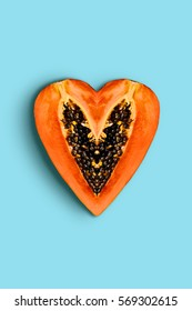 Heart shape papaya fruit creative design on blue background top view