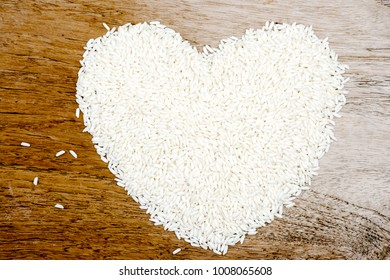 heart shape pile of uncooked sticky rice on old wooden background.copy space for add text