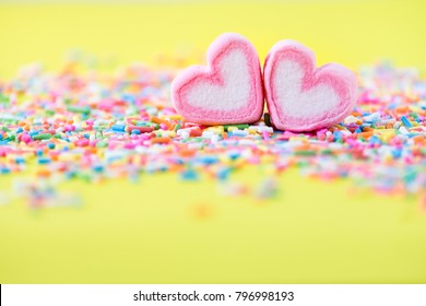 Heart shape of pink marshmallow on sprinkles on green background with copy space. Concept for valentine's day love celebration.