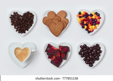 Heart shape plate with cookies, candy, chocolate and coffee cup on white background.