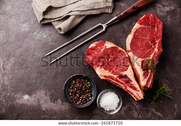 Heart shape Raw fresh meat Ribeye Steak with rosemary, pepper and salt on stone slate background