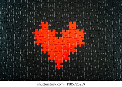 Heart shape red puzzle pieces out of blacks