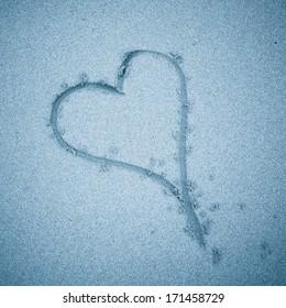 Heart shape in sand in blue tones