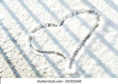 Heart shape in the snow behind the bars.
