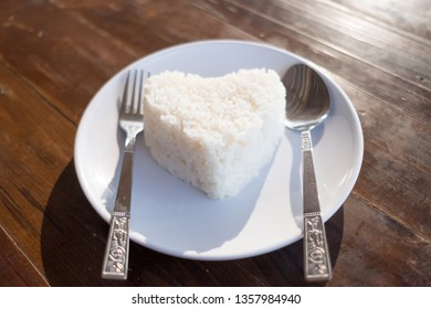 Heart shape steamed rice with spoon and fork on white dish