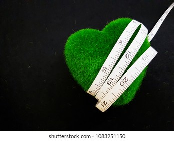 Heart shape symbol wrapped around with measurement tape. Concept of slimming and health