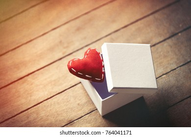 Heart shape toys and gift box on wooden background. Image in old color style