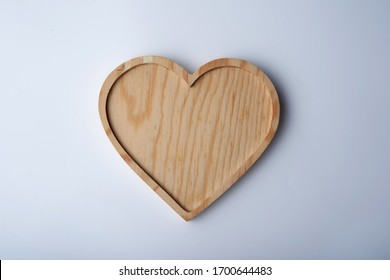 Heart shape wooden tray on white background