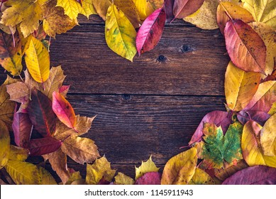 Heart shaped arrangement of autumn leaves over wooden background. Space for text