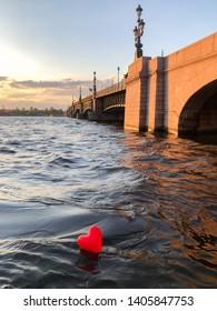 Heart shaped balloon on the Neva River at sunset, Trinity bridge on background. Love for St. Petersburg.