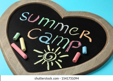 Heart shaped blackboard with text SUMMER CAMP, drawing and chalk sticks on color background