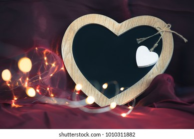 Heart shaped blackboard wth no text, fairy lights and purple silk