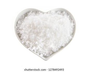 Heart shaped bowl of Flor de Sal, a Portuguese salt derived from the evaporation of sea water, viewed from above isolated on white