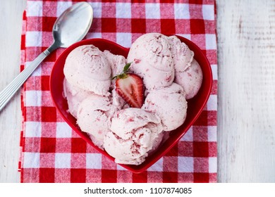 Heart shaped bowl with homemade strawberry ice cream on red checkered cloth with spoon