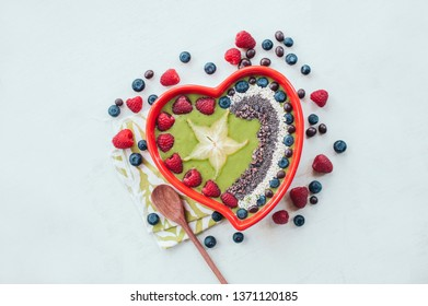 Heart shaped bowl of raspberry, blueberry, cocao nibs, wooden spoon near, isolated over white backgound. Spinach bowl. Fresh fruit