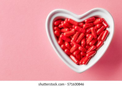 heart shaped bowl of red medicine pills on pink background, top view