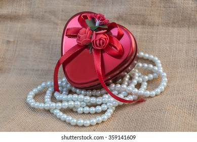 Heart shaped box on a sack adorned with beaded necklace.