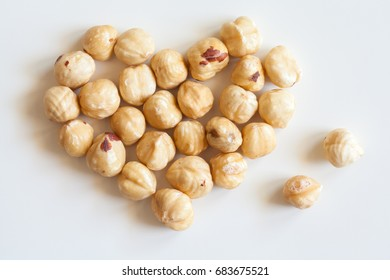 Heart shaped bunch of roasted hazelnuts on white background.