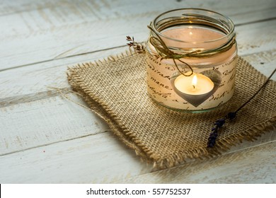Heart shaped candle in jar with twine and delicate field flower on burlap cloth, white plank wood background, Valentine,wedding decoration,handmade