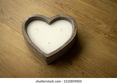 Heart shaped candle sitting on a wooden floor with lots of copy space for own text
