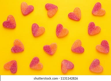 Heart shaped candy pattern on a yellow background. Jelly candies viewed from above. Top view. Repetition concept