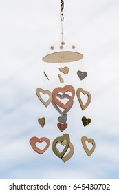 Heart shaped ceramic wind mobile hanging with defocused blue sky in background.