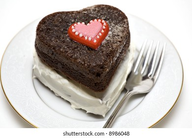 A heart shaped chocolate cake on plate with fork.