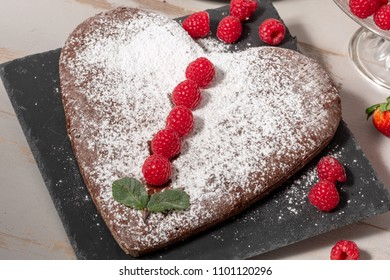 a heart shaped chocolate cake with strawberries