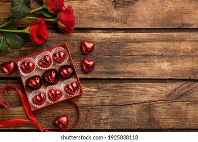 Heart shaped chocolate candies and bouquet on wooden table, flat lay. Space for text