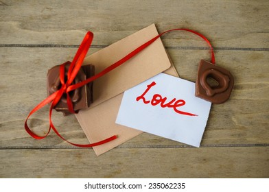 Heart shaped chocolate pieces with red ribbon, letter with Love message and coffee