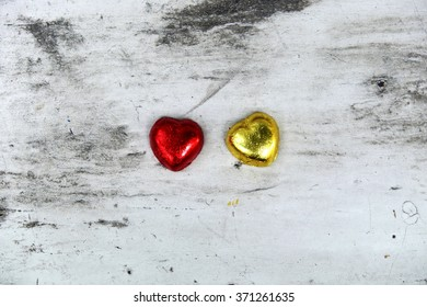 Heart shaped chocolates on white wooden background with black marks. Space for texts. Focus on chocolates.