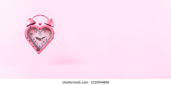 Heart shaped clock on pink background.  Valentines day and love infitity and duration concept. Horizontal, banner wide screen format
