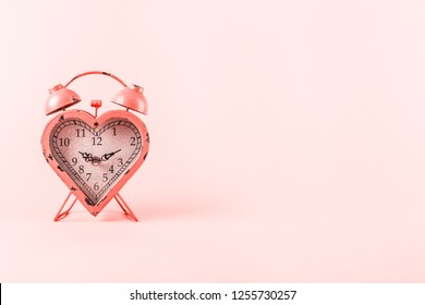 Heart shaped clock on pink background.  Valentines day and love infitity and duration concept. Horizontal. Living coral theme - color of the year 2019