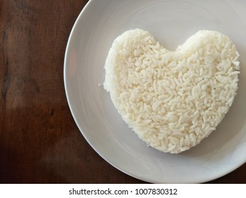 Heart shaped from cooked white rice on white ceramic dish at right side of image with copy space