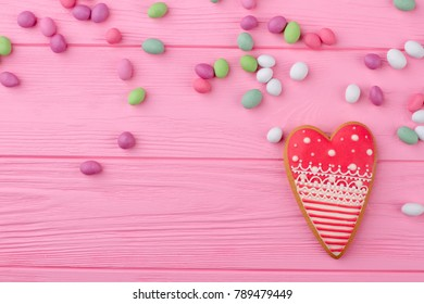 Heart shaped cookie and copy space. Colorful candies on pink wooden background. Valentines Day greeting background.