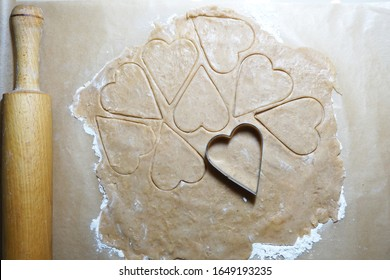 Heart shaped cookie cutters cutting out holiday cookies.