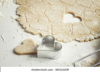 Heart shaped cookie cutters cutting out holiday sugar cookies