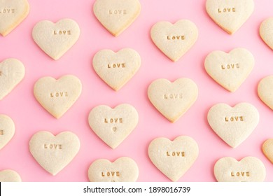 Heart shaped cookie mosaic with the word LOVE on a pink background. Valentine's Day, Mother's Day, anniversary. Top view.