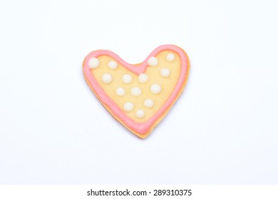 Heart shaped cookie with pink sugar icing isolated on white