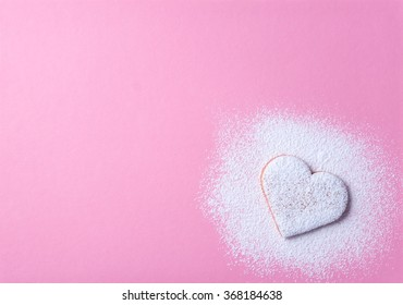 Heart shaped cookie with sugar icing, on pink natural paper background