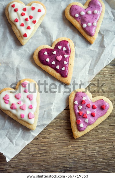 Heart shaped cookies close up for Valentine day - homemade festive decorated pastry biscuits cookies on baking paper, valentine love concept
