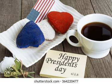 Heart shaped cookies color red, blue, white. Cup of coffee (tea), USA flag, decoration on old wooden table. Patriotic Breakfast Concept - Happy Presidents day