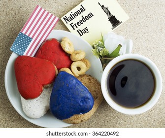 Heart shaped cookies color red, blue, white. Cup of coffee (tea), USA flag, decoration on old wooden table. Patriotic Breakfast Concept - National Freedom Day.