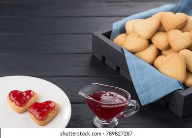 Heart shaped cookies decorated for Valentine's Day. Free space for text. Box with heart shaped cookies. Two heart shaped cookies with jam on a black wooden table. Like postcard