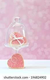 Heart shaped cookies on glass stand with white ribbon
