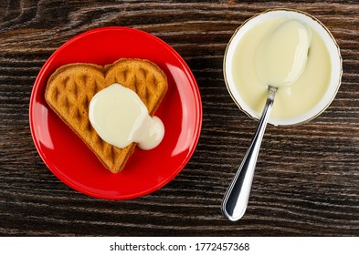 Heart shaped cookies poured condensed milk in red glass saucer, teaspoon in bowl with condensed milk on dark wooden table. Top view