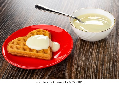 Heart shaped cookies poured condensed milk in red glass saucer, teaspoon in bowl with condensed milk on dark wooden table