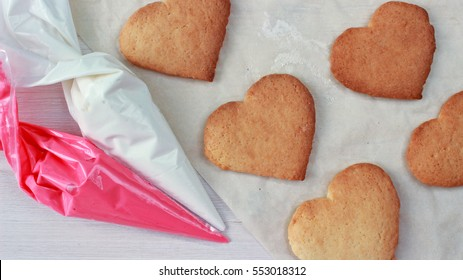 heart shaped cookies ready for decoration with pastry bags on light wooden background