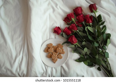 heart shaped cookies and red roses on white bed